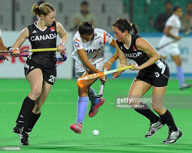 Kristine Wishart and Danielle Hennig of Canada block Rani Rampal of India during the women's field hockey match between India and Canada of the FIH...