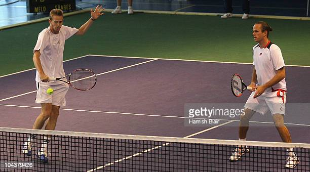 Kristof Vliegen of Belgium plays a backhand with team mate Xavier Malisse of Belgium looking on during their doubles match against Marcelo Melo and...