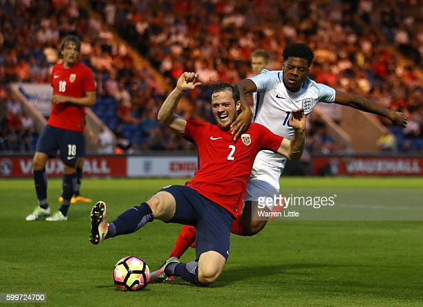 Kristoffer Haraldseid of Norway is tackled by Chuba Akpom of England during the European Under 21 Qualifier match between England U21 V Norway U21 at...
