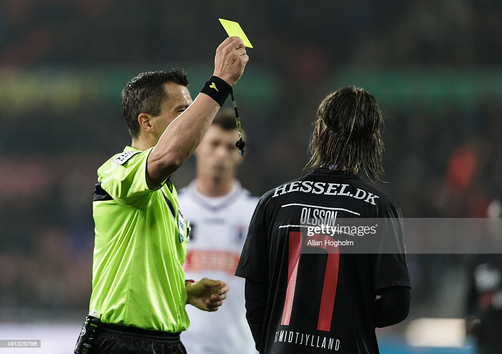 Kristoffer Olsson of Midtjylland receives a yellow card from Referee Michael Tykgaard during the Danish Alka Superliga match between FC Midtjylland and AGF Aarhus at MCH Arena on October 4, 2015 in Herning, Denmark.