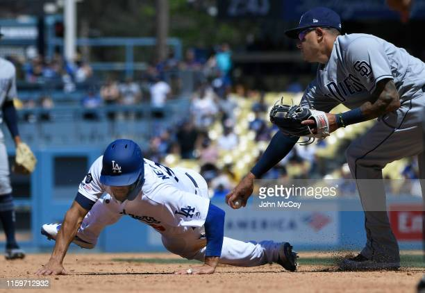 Kristopher Negron of the Los Angeles Dodgers avoids a tag at third base by Manny Machado of the San Diego Padres during a run down in the fourth...