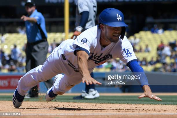 Kristopher Negron of the Los Angeles Dodgers dives into thrid base against the San Diego Padres in the fourth inning at Dodger Stadium on August 4,...