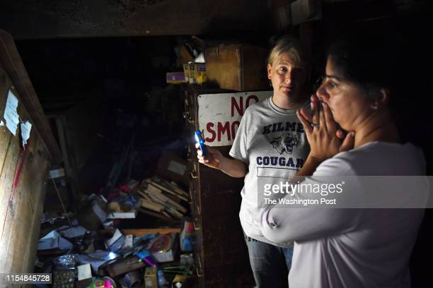Kristy Peterkin center shows the basement of her parent's business Ayers Variety and Hardware that was flooded by Monday's flash flood to friend...