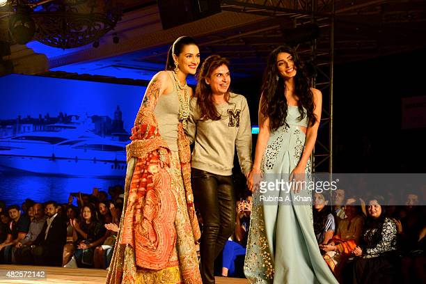 Kriti Sanon Designer Monisha Jaising and Pernia Qureshi walk the runway during Monisha Jaising's couture collection for the Fashion Design Council of...