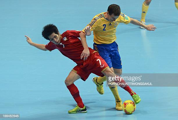 Kritsada Wongkae of Thailand battles for the ball with Mykhaylo Romanov of Ukraineduring their first round football match of the FIFA Futsal World...