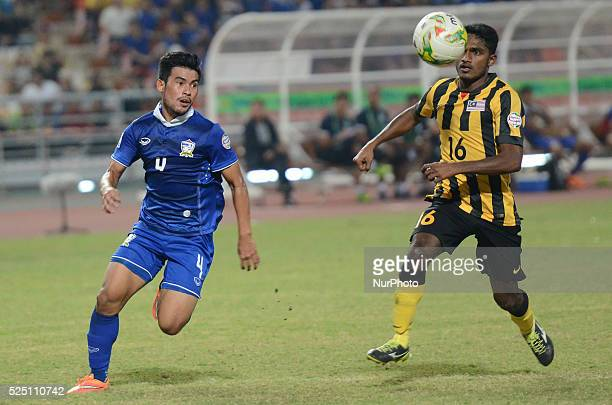 Kroekrit Thaweekarn of Thailand vies with Kunanlan Subramaniam of Malaysia during the AFF Suzuki Cup 2014 final round 1st leg Thailand Malaysia at...