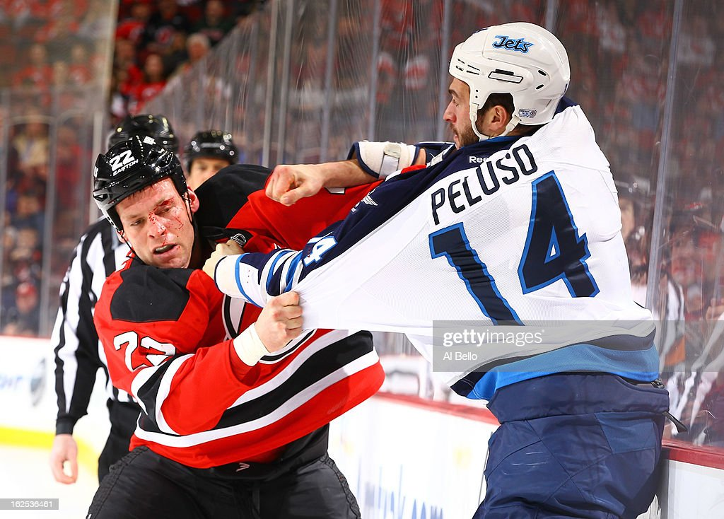 Krys Barch #22 of the New Jersey Devils fights with Anthony Peluso #14 of the Winnipeg Jets during their game at the Prudential Center on February 24, 2013 in Newark, New Jersey.