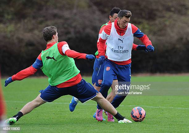 Krystain Bielik and Mesut Ozil of Arsenal during a training session at London Colney on February 14 2015 in St Albans England