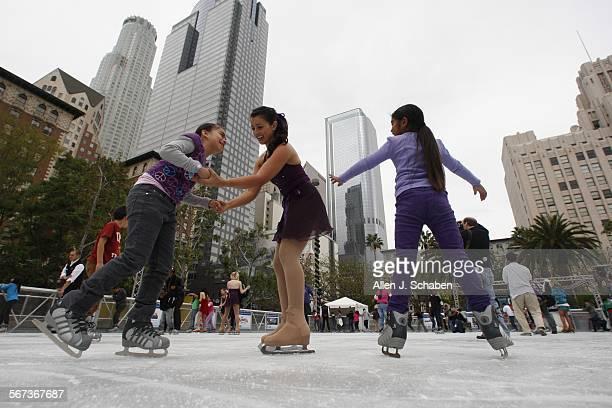 Krystal Davis center of the LA Ice Theater teaches San Pedro Street Elementary School students Ashley Sagahon left and Bixey Vargas right how to ice...