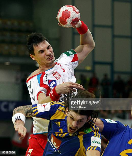 Krysztof Lijewski of Poland tackles Frederik Petersen of Sweden during the Men's Handball European Championship Group C match between Poland and...