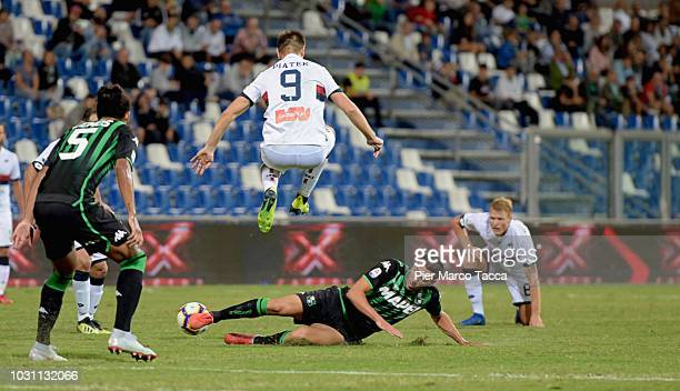 Krysztof Piatek of Genoa CFC competes for the ball with Mehdi Bourabia of US Sassuolo during the serie A match between US Sassuolo and Genoa CFC at...