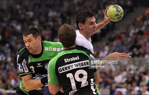 Kryzstof Lijewski of Hamburg is challenged by Ferenc Ilyes and Martin Strobel of Lemogo during the Toyota Handball Bundesliga match between HSV...