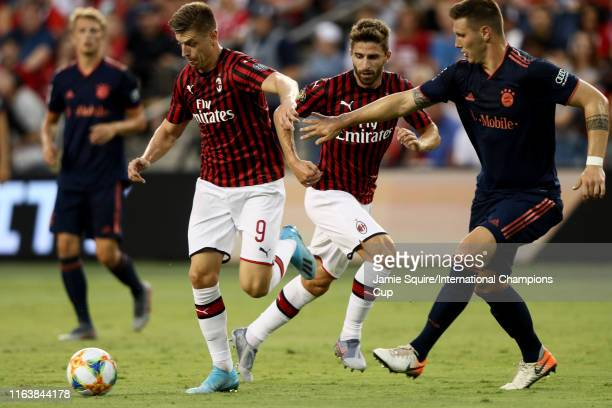 Krzystof Piatek of Milan dribbles beyond the defense of Niklas Süle of Bayern Munich during the second half of the match at Children's Mercy Park on...