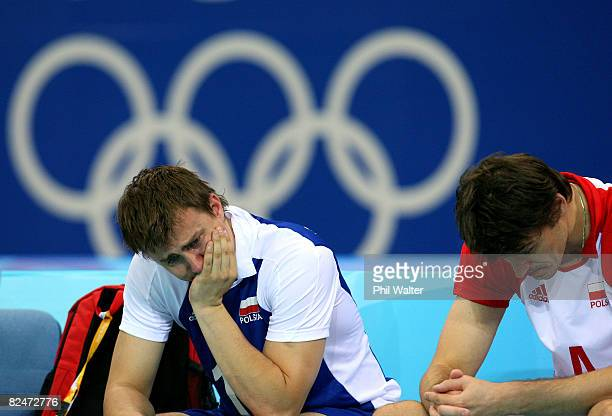 Krzysztof Ignaczak and Daniel Plinski of Poland react after losing against Italy during the volleyball event at the Capital Indoor Stadium during Day...
