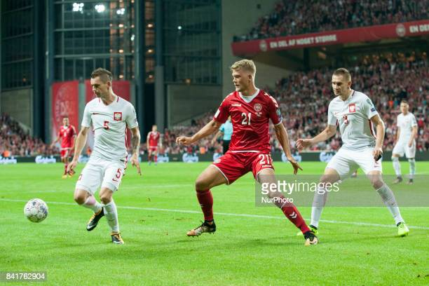 Krzysztof Maczynski and Artur Jedrzejczyk fight for the ball with Andreas Cornelius of Denmark during the FIFA World Cup 2018 Qualifying Round...