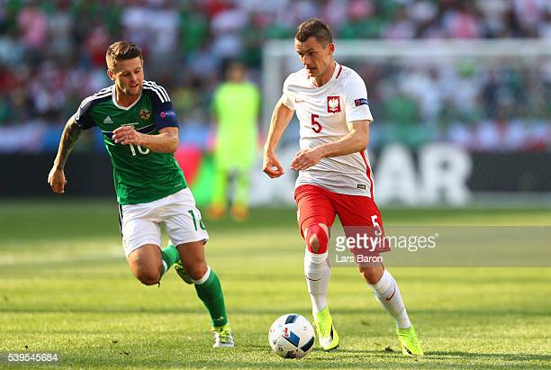 Krzysztof Maczynski of Poland and Oliver Norwood of Northern Ireland compete for the ball during the UEFA EURO 2016 Group C match between Poland and...