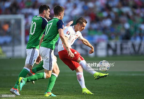 Krzysztof Maczynski of Poland controls the ball under pressure of Kyle Lafferty and Paddy McNair of Northern Ireland during the UEFA EURO 2016 Group...