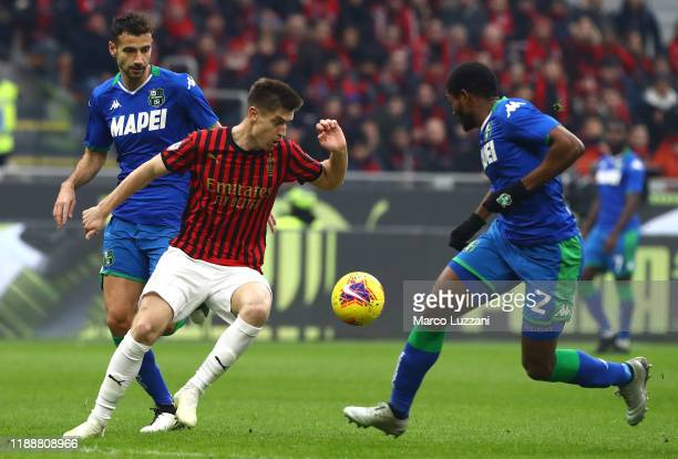Krzysztof Piatek of AC Milan competes for the ball with Gianmarco Ferrari and Marlon of US Sassuolo during the Serie A match between AC Milan and US...