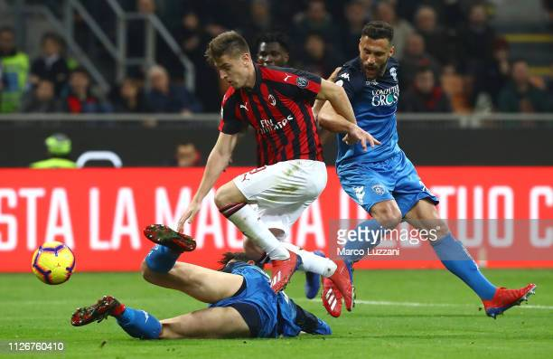 Krzysztof Piatek of AC Milan competes for the ball with Matias Silvestre and Cristian Dell Orco of Empoli during the Serie A match between AC Milan...