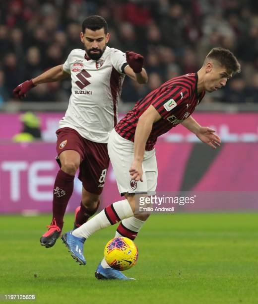 Krzysztof Piatek of AC Milan is challenged by Tomas Rincon of Torino FC during the Coppa Italia Quarter Final match between AC Milan and Torino at...