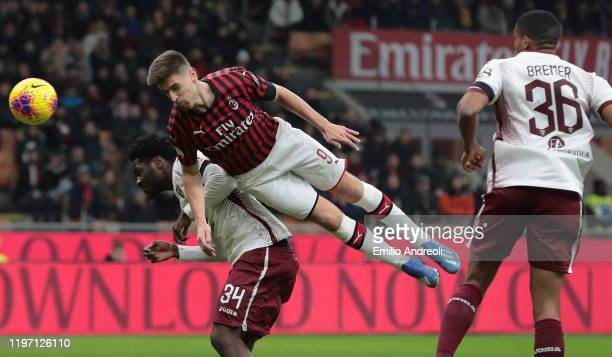 Krzysztof Piatek of AC Milan jumps for the ball against Ola Aina of Torino FC during the Coppa Italia Quarter Final match between AC Milan and Torino...