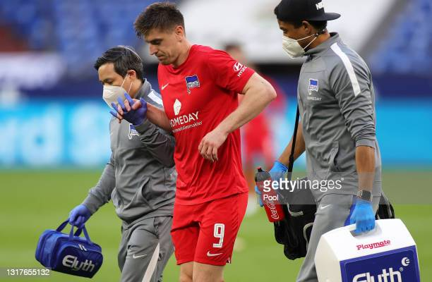 Krzysztof Piatek of Hertha BSC is helped by medical staff following an injury during the Bundesliga match between FC Schalke 04 and Hertha BSC at...