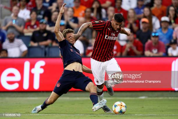 Krzysztof PiAtek of Milan tries to dribble through the slide tackle attempt of Thomas Müller of Bayern Munich during the first half of the match at...