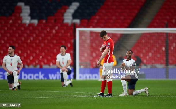 Krzysztof Piatek of Poland points to his respect badge as Raheem Sterling of England takes a knee in support of the Black Lives Matter movement prior...