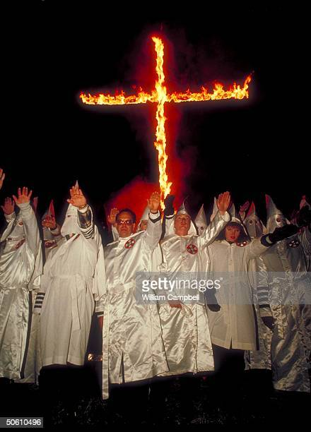 Ku Klux Klan Grand Wizard Thom Robb leading fellow robed hooded Klansmen in white power salute in front of burning cross at KKK rally