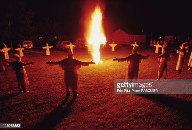 Ku Klux Klan In United StatesKlansmen form a circle around a burning cross Their arms spread wide symbolize the association of each member among the...