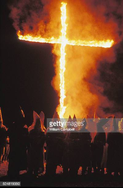 Ku Klux Klan members gather in front of an image of a burning cross