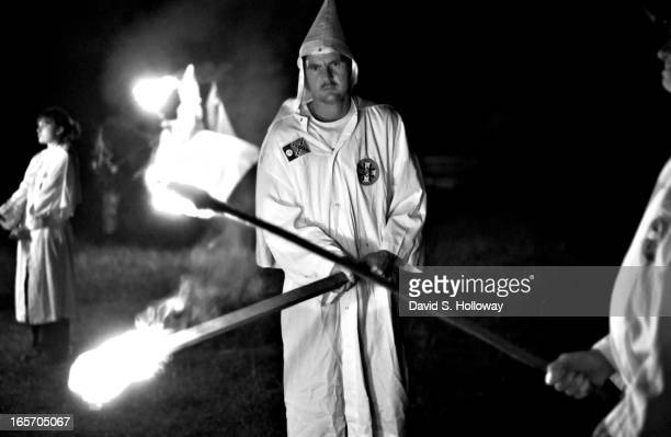 Ku Klux Klan members light torches as they begin a crosslighting ceremony at the Aryan Nations sponsored White Heritage Days Festival which was held...