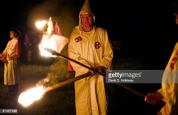 Ku Klux Klan members light torches as they begin a crosslighting ceremony at the Aryan Nations sponsered White Heritage Days Festival which was held...