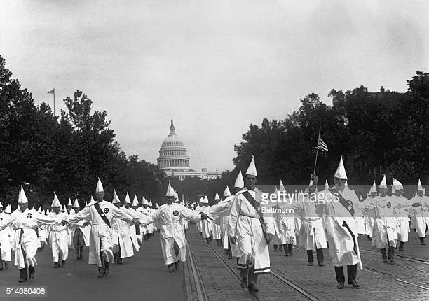 Ku Klux Klan members parade down Pennsylvania Avenue from the capitol to the treasury in Washington DC on August 8 1925