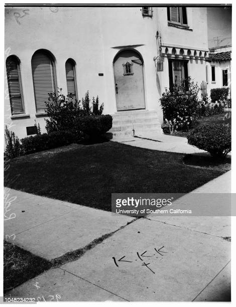 Ku Klux Klan warning , 01 April 1952. On sidewalk at 2633 South Ridgeley Drive;Reporter looking on.2633 South Ridgeley Drive; Los Angeles;...