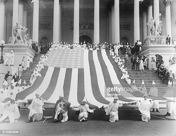 Ku Klux Klansmen draping giant American flag over Capitol steps