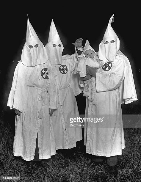 Ku Klux Klansmen in a secret night meeting Photograph with infant