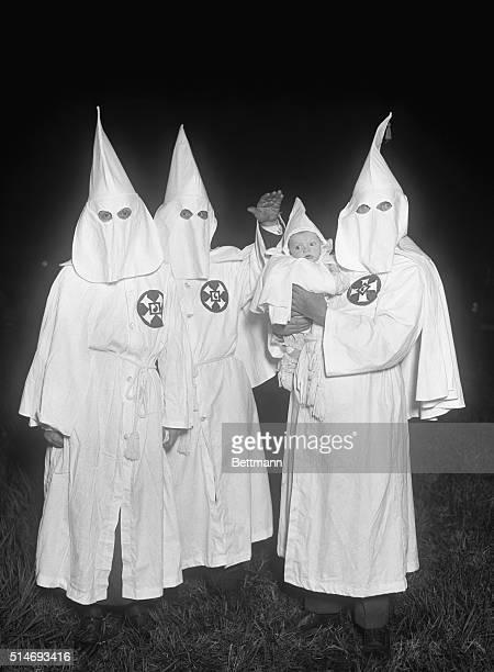 Ku Klux Klansmen in a secret night meeting. Photograph with infant.