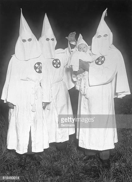 Ku Klux Klansmen in a secret night meeting with an infant. Photograph. BPA2