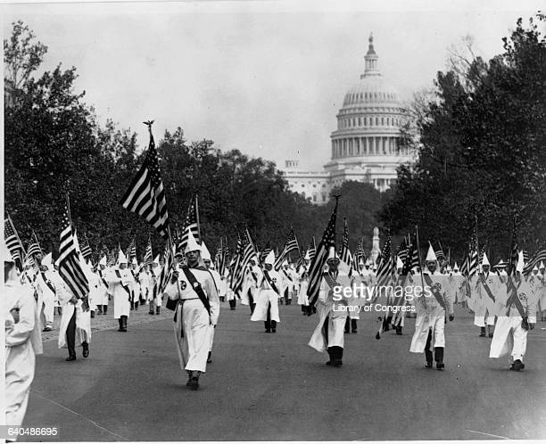 Ku Klux Klansmen parade on Pennsylvania Avenue with the Capitol in the background 1920s