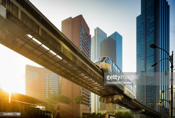 kuala lumpur elevated monorail in chow kit back lit by sunrise - kuala lumpur stock pictures, royalty-free photos & images