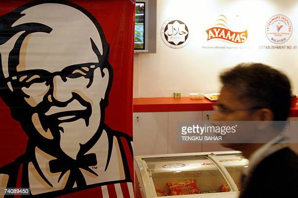 A delegate walks past a banner of KFC's Colonel Sanders at an exhibition booth during the World Halal Forum in Kuala Lumpur 07 May 2007 Islamic...