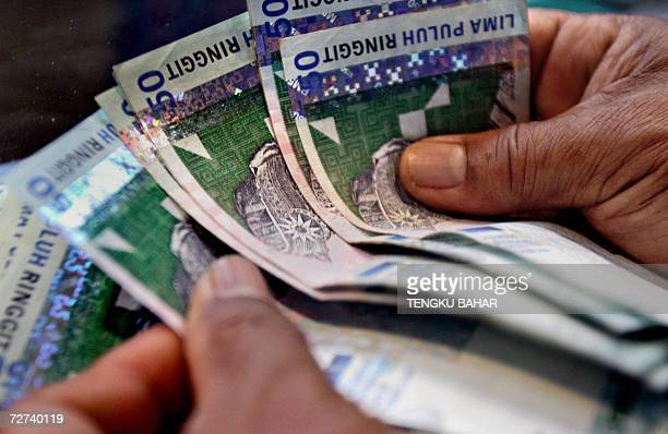 A money changer counts Malaysian ringgit bank notes at a foreign exchange booth in downtown Kuala Lumpur 06 December 2006 Malaysia's currency has...