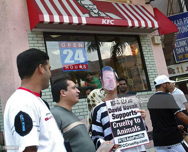 An activist from the People for the Ethical Treatment of Animals AsiaPacific dressed in striped prison jumpsuits and mask bearing the image of KFC...