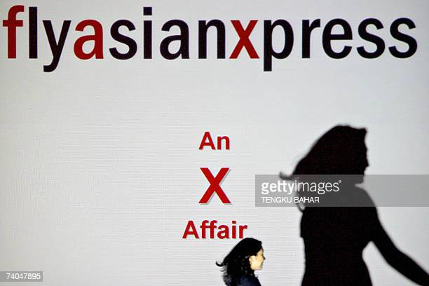 Kuala Lumpur, MALAYSIA: An Air Asia employee walks in front of a projection screen with advertising for Fly Asian Xpress, the operator for AirAsiaX,...