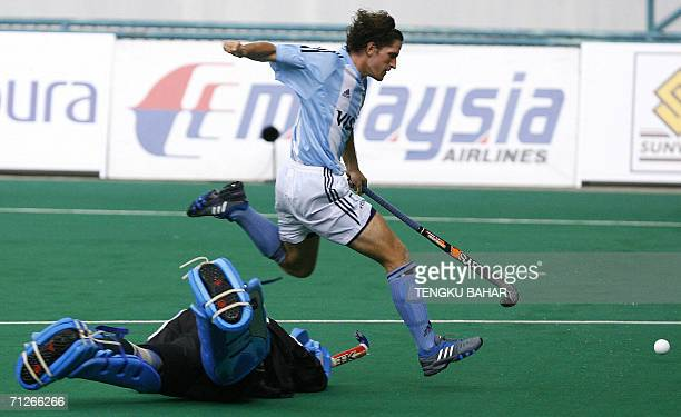 Argentina's Innocente Tomas Argento jumps over Pakistan's goalkeeper Salman Akbar while chasing the ball during the fifth day of the Sultan Azlan...