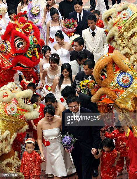 Couples walk past a troupe of lion dancers as they enter a ceremonial hall during a mass wedding at a Buddhist temple in Kuala Lumpur 07 July 2007...