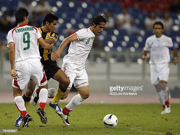 Iranian midfielder Ali Karimi takes the ball against Malaysian player in the group C of the Asian Football Cup 2007 at the Bukit Jalil stadium in...