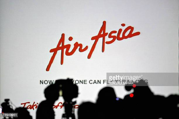 Kuala Lumpur, MALAYSIA: Television camera crew are silhouetted against a projection screen during a signing ceremony between AirAsia X and Airbus in...