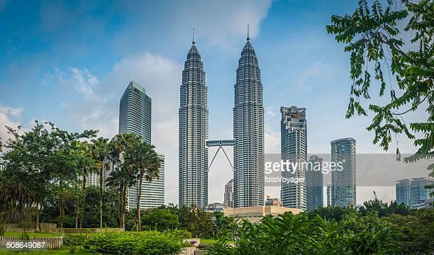 kuala lumpur petrona torres arranha-céus, emoldurado por folhagem klcc malásia - torres petronas - fotografias e filmes do acervo